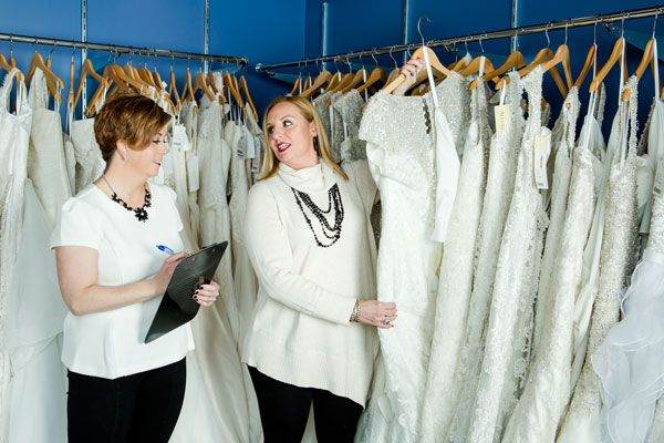 Owners Heidi Nicholson and Lisa Almeida (holding Allure® gown) selecting this season's most popular gowns to display in the storefront. They make multiple international and national buying trips each year to bring their customers the very best the fashion world has to offer. Photo ©Shawn Black Photography