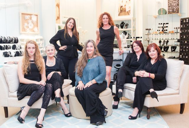 The Gilded Gown stylists (L to R): Grace Alexander (owner's daughter), Vicki Senape, Elizabeth Ethridge (owner's sister), Heather Lynn, Andrea Yeager, Emily Muse. (Center, in blue top): Owner Jacqui Wadsworth.