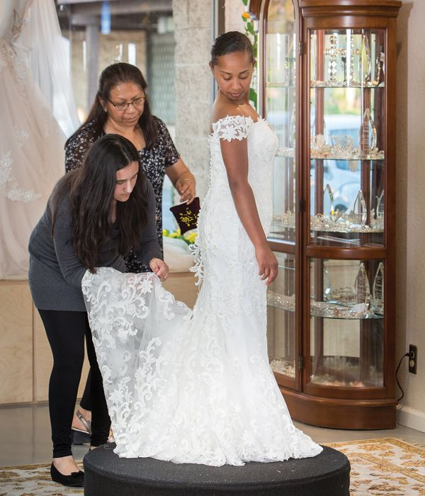 Consultant Crystal, who has been with Ferndales for 12 years, and the salon's seamstress of 14 years, Yolanda, put final touches on a bride's dress.