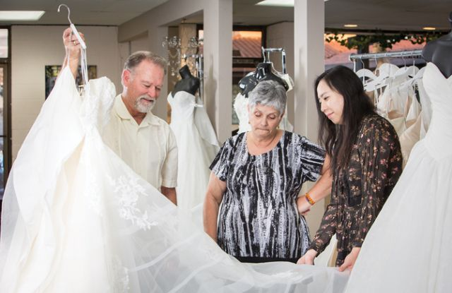 Ferndales Owners Tom and Connie Linnert admire a dress from Estee' Couture Bridal with Designer/Owner Estee Yao.