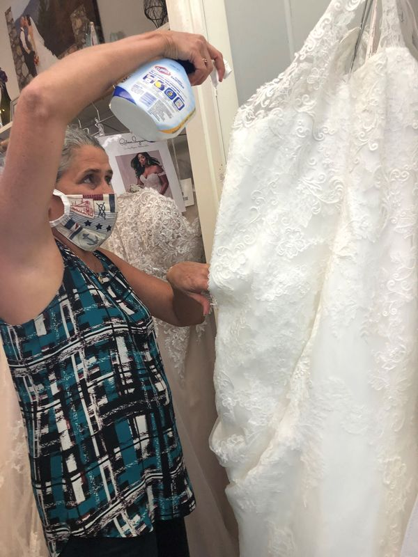Country Bridals owner Cathy Furze sprays a bridal gown with a fabric sanitizer, a practice she instituted after her 18-year-old boutique reopened on May 11 after nearly two months of being closed due to the novel coronavirus pandemic. (Courtesy of Country Bridals & Formal Wear)