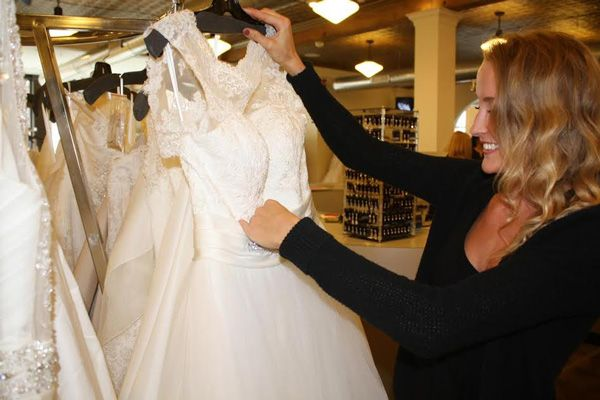 A bridal consultant selecting a gown for her customer to try on.