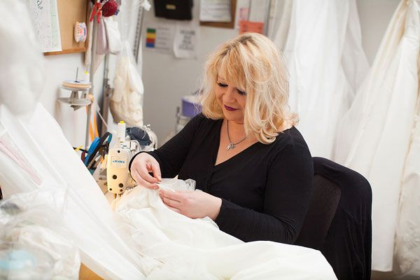 Seamstress Alena Lipovsky hand stitches alterations on a bridal gown. Photo credit: Topher Stevenson / J Thomas Photography