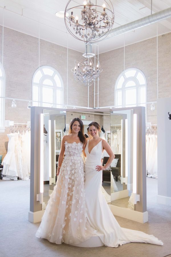Full-length lights over the three-way mirrors at Little White Dress Bridal Shop in Denver prevent shadows on the dresses, while chandeliers show off the high ceilings and large space of the salon.