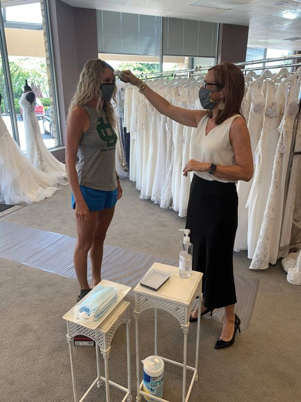 Wendy's Bridal general manager Lilly Stalnaker takes the temperature of a bride at the entrance of the Dublin, Ohio-based boutique. Temperature scans were one of the many policies Wendy's instituted amid COVID-19. (Courtesy of Wendy's Bridal)